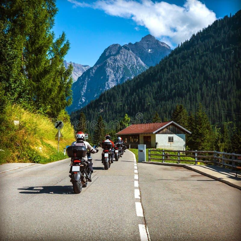 Grupa rowerzyści na drodze w Alps obrazy stock