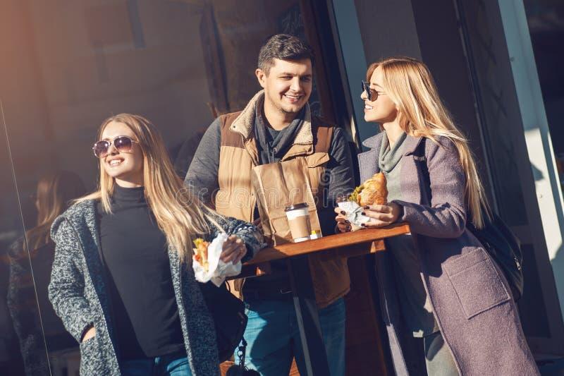 Grupa rozochoceni młodzi ludzie opowiada, pije kawę i je croissant w cukierniany plenerowym na słonecznym dniu, Pojęcie więź, obraz royalty free