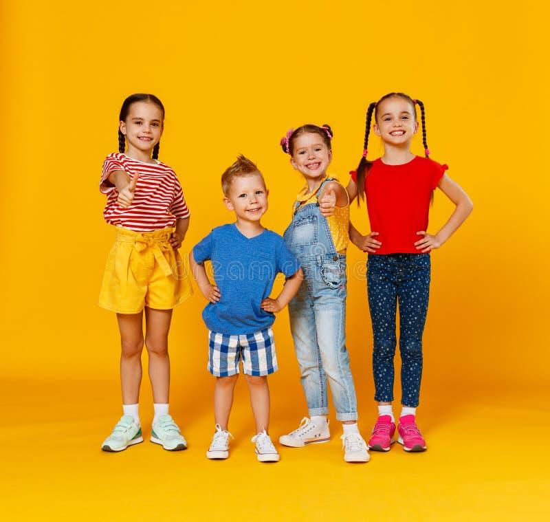 Grupa rozochoceni szcz??liwi dzieci na barwionym ? zdjęcie stock