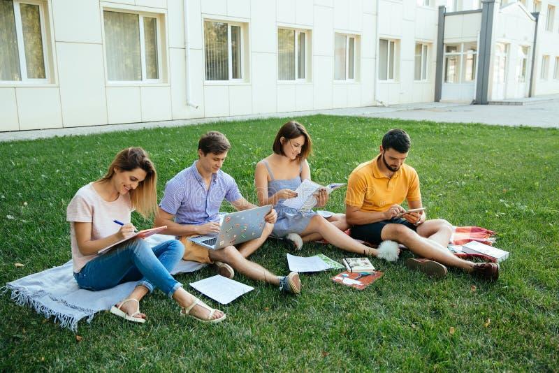 Grupa rozochoceni uczni nastolatkowie w przypadkowych strojach z nutowymi książkami i laptop studiujemy outdoors obraz royalty free