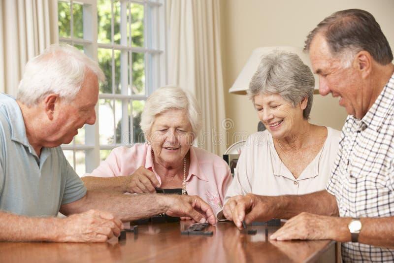 Grupa senior pary Cieszy się grę domina W Domu zdjęcie stock