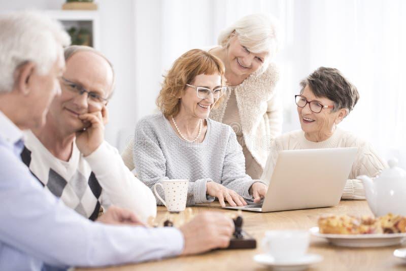 Grupa seniory siedzi przy stołem fotografia stock