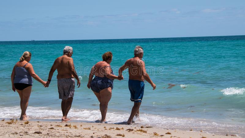 Grupa seniory wchodzić do ocean zdjęcia royalty free