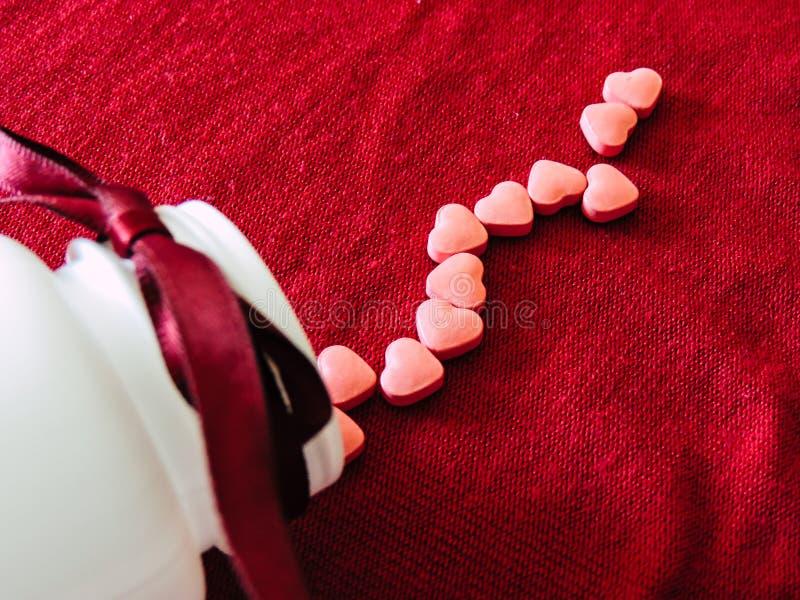 Grupa serce pastylki z białą butelką na czerwonym sukiennym tle czerwona róża obraz royalty free