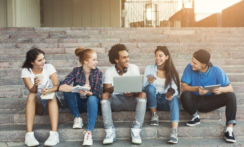 Grupa siedzi na kampus?w schodkach rozochoceni wiek dojrzewania obraz royalty free