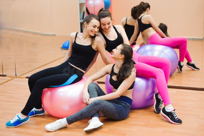 Grupa sportive ludzie w gym pojęcia o styl życia i - Szczęśliwi sporty przyjaciele w ciężaru pokoju podczas gdy trenujący - fotografia stock