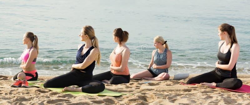 Grupa sporty dziewczyny ćwiczy różnorodne joga pozycje podczas t zdjęcia stock