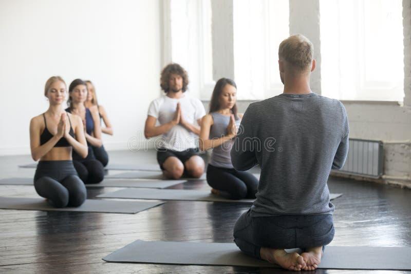 Grupa sporty ludzie w vajrasana ćwiczeniu z instruktorem zdjęcie royalty free