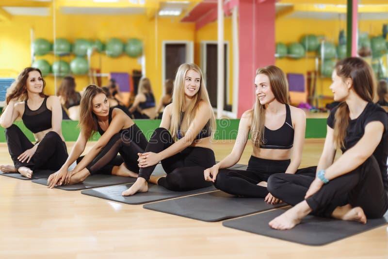 Grupa sporty szczęśliwe kobiety siedzi na gym podłoga, ucznie opowiada i odpoczywa po tym jak joga klasa ma otwartego dyskusi abo obraz royalty free