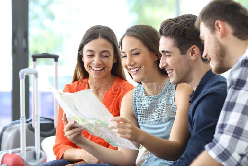 Grupa sprawdza papierową mapę przyjaciele planuje wakacje obrazy stock