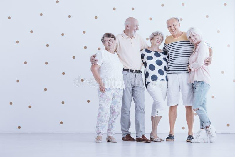 Grupa starsi przyjaciele ściska each inny w białym studiu z zdjęcie stock