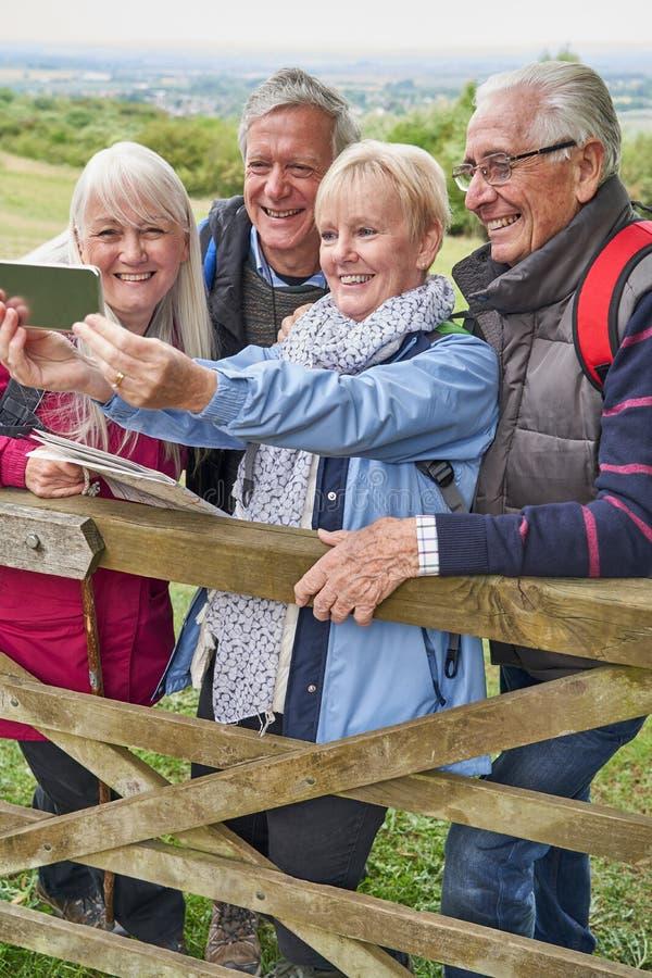 Grupa Stoi Bezczynnie bramę I Bierze Selfie Na telefonie komórkowym Starszy przyjaciele Wycieczkuje W wsi fotografia stock