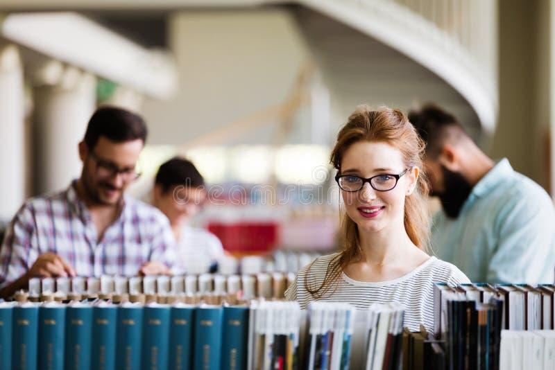 Grupa studenci collegu studiuje przy biblioteką fotografia royalty free