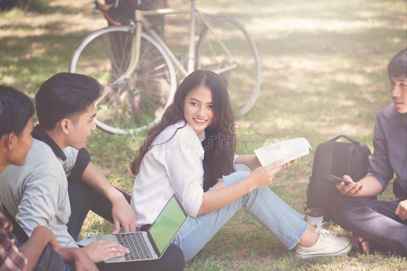 Grupa studenci uniwersytetu pracuje outside wpólnie w kampusie, obrazy royalty free