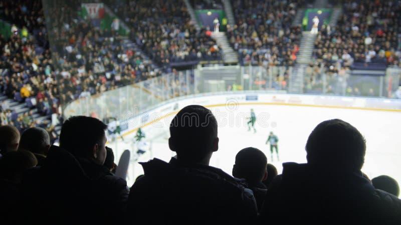 Grupa sylwetki młodzi ludzie ogląda hokeja dopasowanie w zamkniętym stadium zdjęcia stock