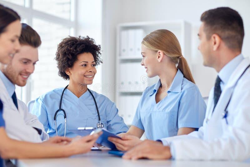 Grupa szczęśliwe lekarki spotyka przy szpitalnym biurem obraz stock