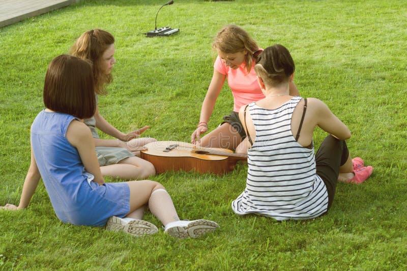 Grupa szczęśliwe nastoletnie dziewczyny ma zabawę z gitarą outdoors Wchodzić na górę z nową muzyką, siedzi na zielonym gazonie w  zdjęcia royalty free