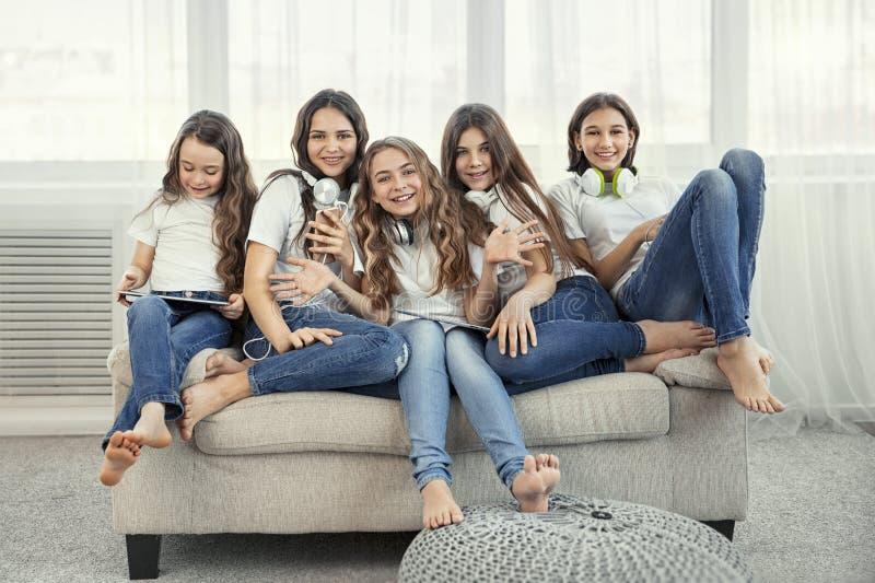 Grupa szczęśliwe nastoletnie dziewczyny z gadżetami Ogólnospołeczne sieci, przyjaźń, technologia i dziecka pojęcie, obrazy stock