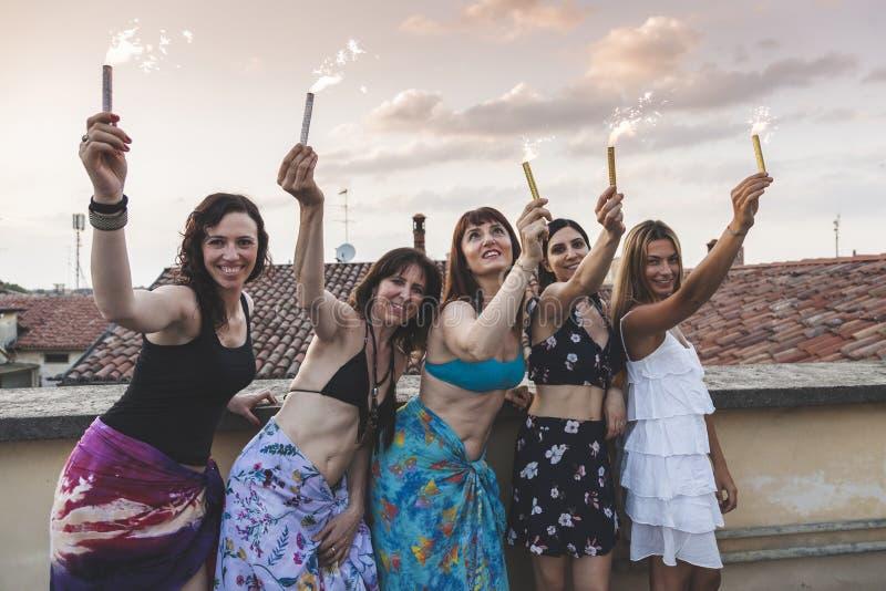 Grupa szczęśliwi żeńscy przyjaciele trzyma sparklers przy dachu przyjęciem obrazy stock