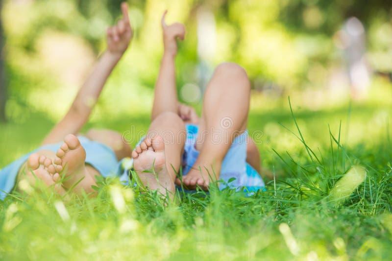 Grupa szczęśliwi dzieci kłama na zielonej trawie zdjęcie royalty free