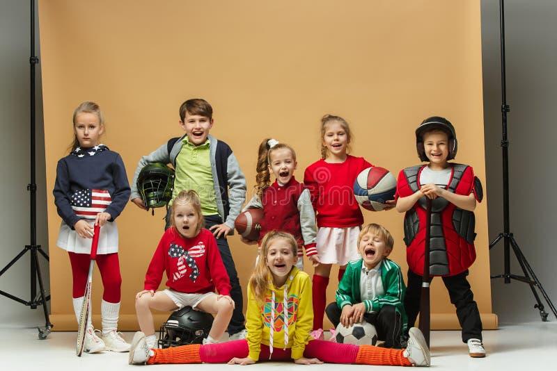 Grupa szczęśliwi dzieci pokazuje różnego sport Pracowniany mody pojęcie Emoci pojęcie obraz royalty free