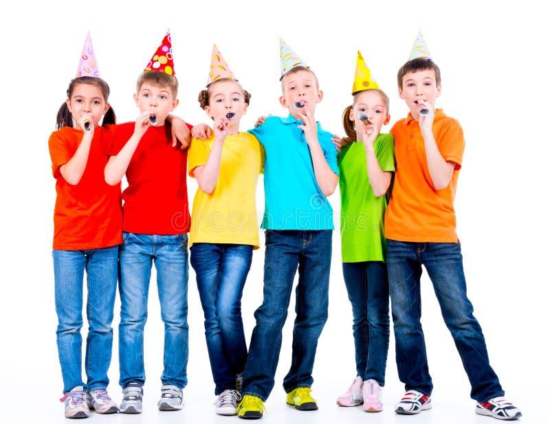 Grupa szczęśliwi dzieci z partyjnymi dmuchawami fotografia stock