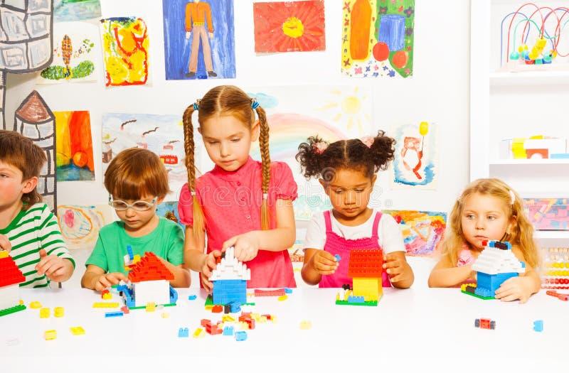 Grupa szczęśliwi dzieciaki bawić się z plastikowymi blokami obraz stock
