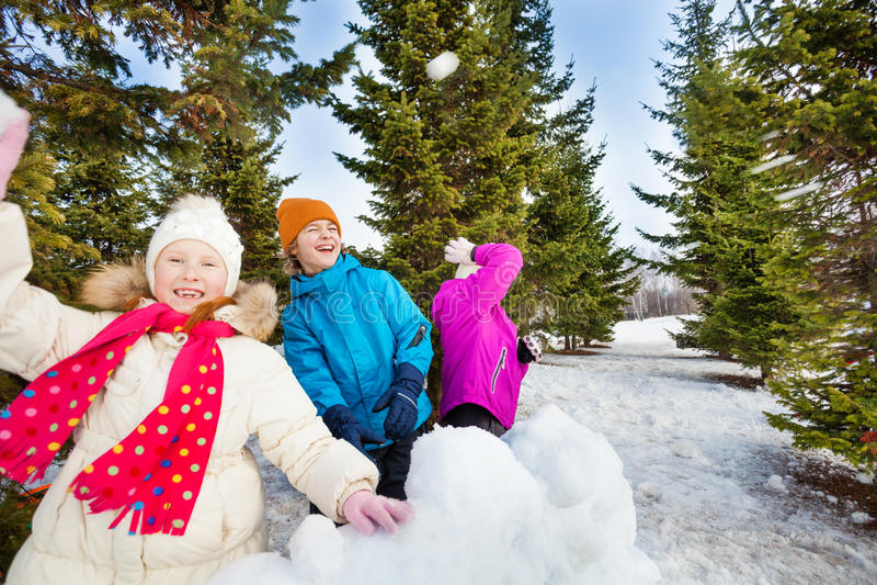 Grupa szczęśliwi dzieciaki rzuca snowballs podczas walki fotografia royalty free