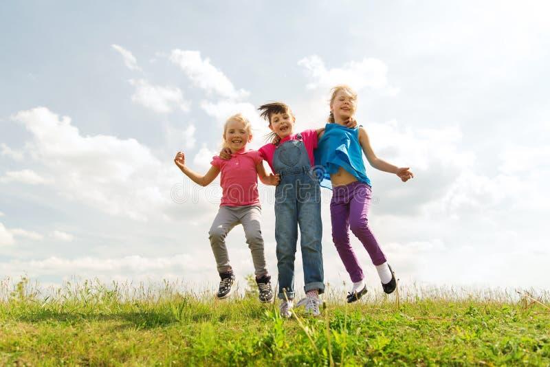 Grupa szczęśliwi dzieciaki skacze wysoko na zieleni polu obraz stock