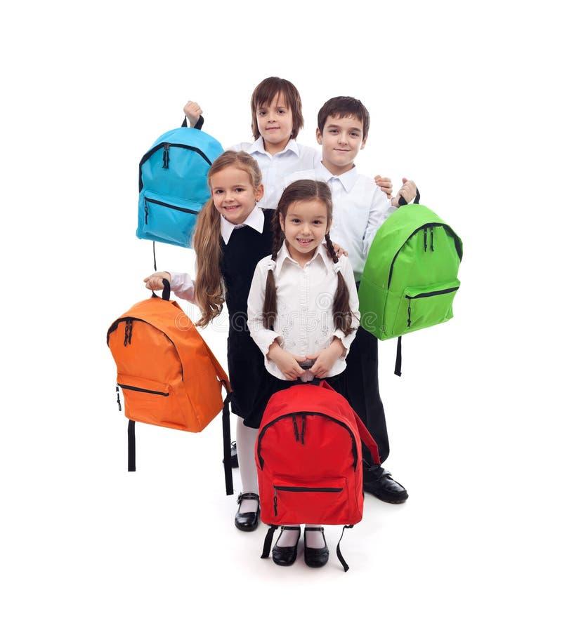 Grupa szczęśliwi dzieciaki z kolorowymi szkolnymi torbami zdjęcie royalty free