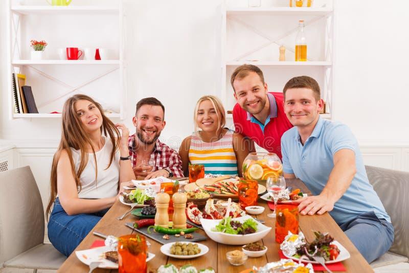 Grupa szczęśliwi młodzi ludzie przy obiadowym stołem, przyjaciele bawi się zdjęcia stock