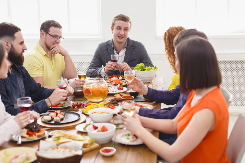 Grupa szczęśliwi młodzi ludzie przy obiadowym stołem, przyjaciele bawi się zdjęcie royalty free