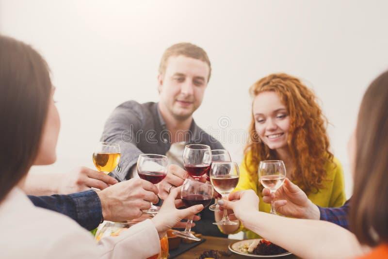 Grupa szczęśliwi młodzi ludzie przy obiadowym stołem, przyjaciele bawi się zdjęcie stock