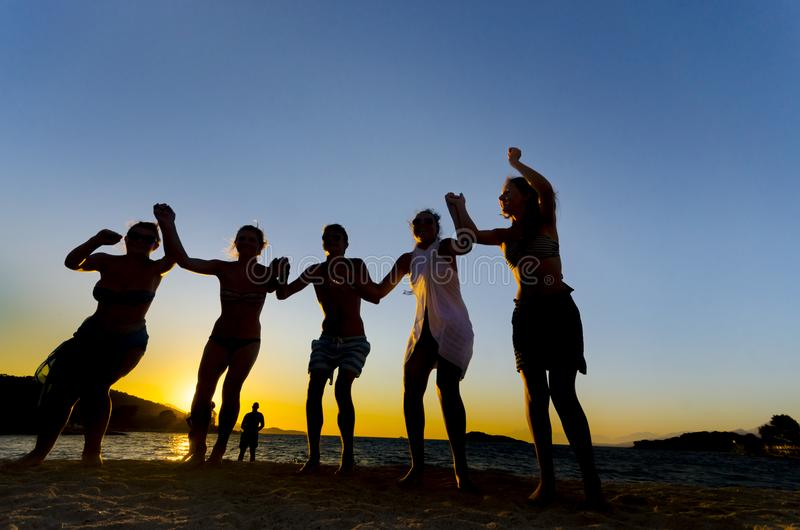 Grupa szczęśliwi młodzi ludzie tanczy przy plażą przy zmierzchem obraz royalty free