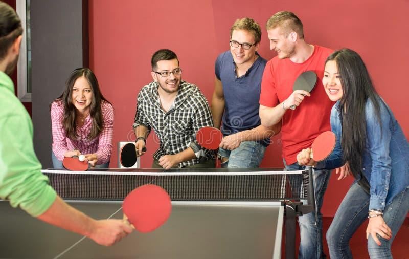 Grupa szczęśliwi młodzi przyjaciele bawić się śwista pong stołowego tenisa obraz royalty free