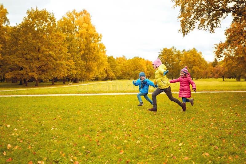 Grupa szczęśliwi małe dzieci biega outdoors zdjęcia royalty free