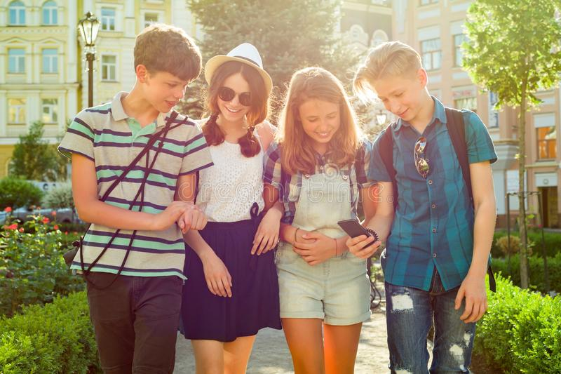 Grupa szczęśliwi nastolatków przyjaciele 13, 14 roku chodzi wzdłuż miasto ulicy obrazy stock