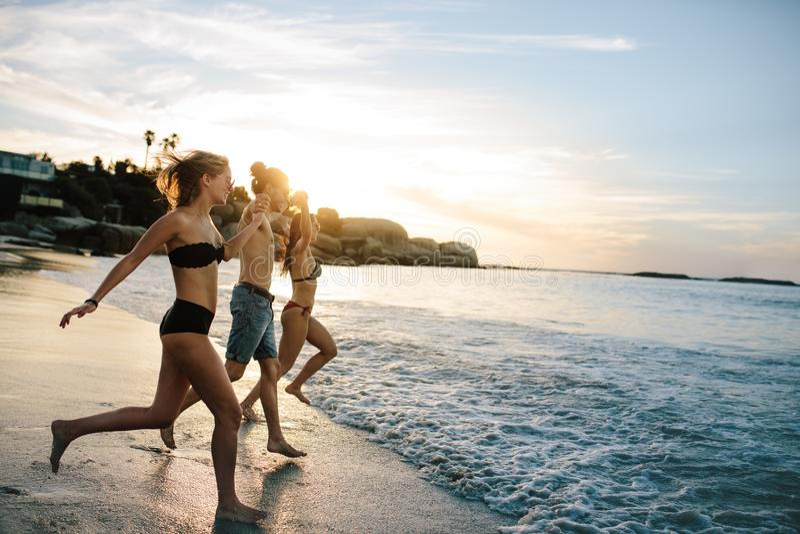 Grupa szczęśliwi przyjaciele biega morze fotografia royalty free