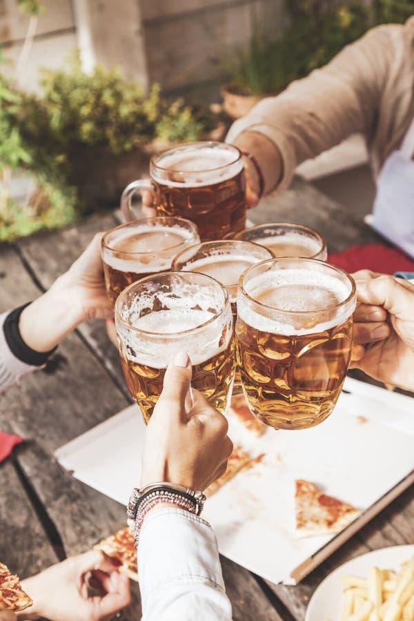 Grupa szczęśliwi przyjaciele pije piwo i je bierze oddaloną pizzę obrazy royalty free