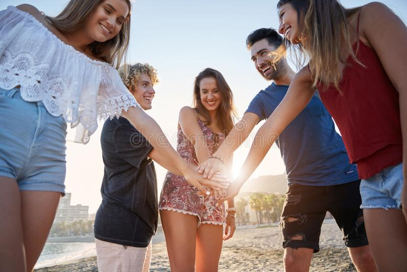 Grupa szczęśliwi przyjaciele trzyma ręki na plaży wpólnie zdjęcia stock