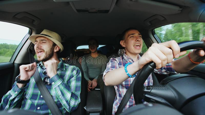 Grupa szczęśliwi przyjaciele w samochodowym śpiewie i tanu podczas gdy prowadnikowa wycieczka samochodowa fotografia stock