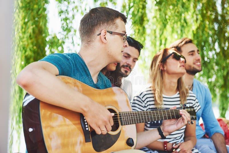 Grupa szczęśliwi przyjaciele z gitarą Podczas gdy jeden one bawić się gitarę i inny dają on round aplauz zdjęcie stock