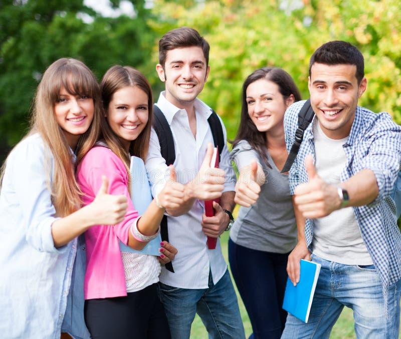 Grupa szczęśliwi ucznie pokazuje ok znaka fotografia stock