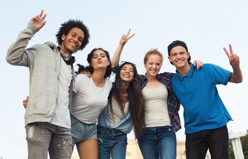 Grupa szczęśliwi wiek dojrzewania obejmuje i ono uśmiecha się przy kamerą obraz royalty free