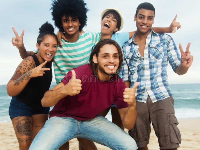 Grupa szczęśliwi wielo- etniczni młodzi dorosli ludzie przy plażą obraz stock