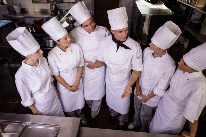 Grupa szefowie kuchni oddziała wzajemnie z each inny w kuchni zdjęcie royalty free
