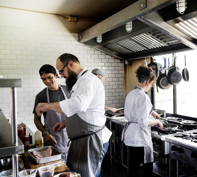 Grupa szefowie kuchni pracuje w kuchni obrazy stock