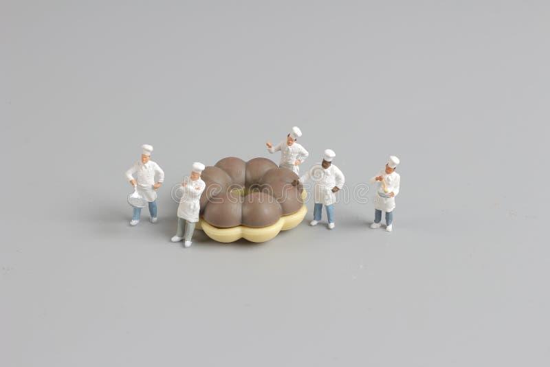 Grupa szefowie kuchni wokoło małych donuts obraz stock