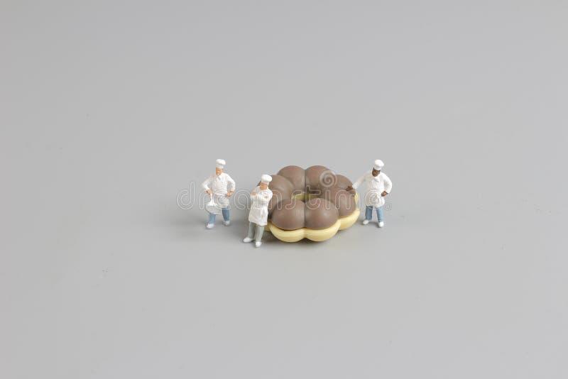 Grupa szefowie kuchni wokoło małych donuts zdjęcia royalty free