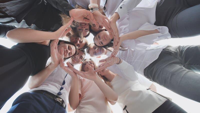 Grupa szkoła średnia uczni spojrzenie przez kształta okrąg tworzył od ich palm Pojęcie życzliwy zdjęcie stock